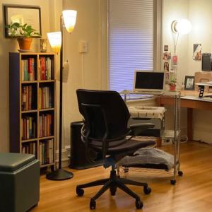 bookshelf, floor lamp, desk chair, and makeshift mobile desk in home office